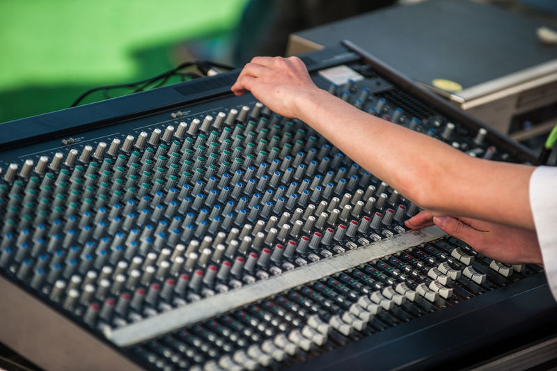 Cropped hands of woman playing sound mixer in recording studio
