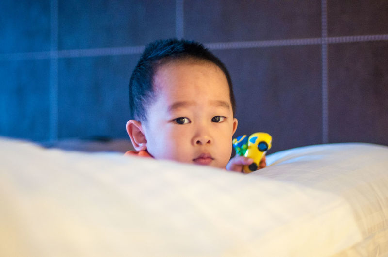 Portrait of cute boy while holding toy on bed at home