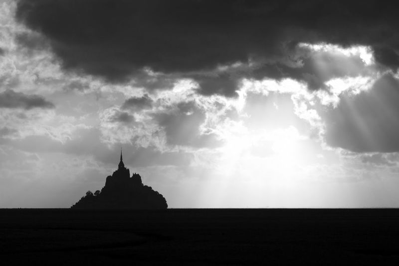 Silhouette of temple against cloudy sky