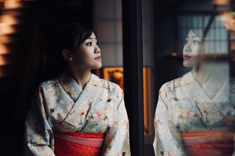 Thoughtful Woman Wearing Traditional Clothing Looking Through Window At Home