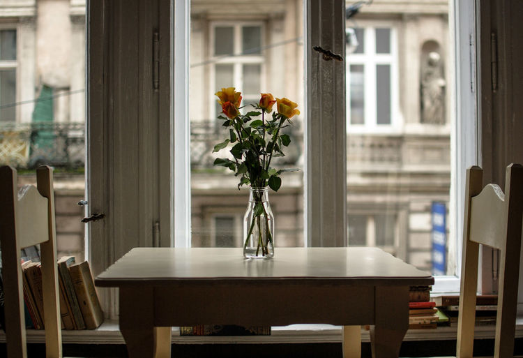 Flowers In Vase On Table By Window At Home