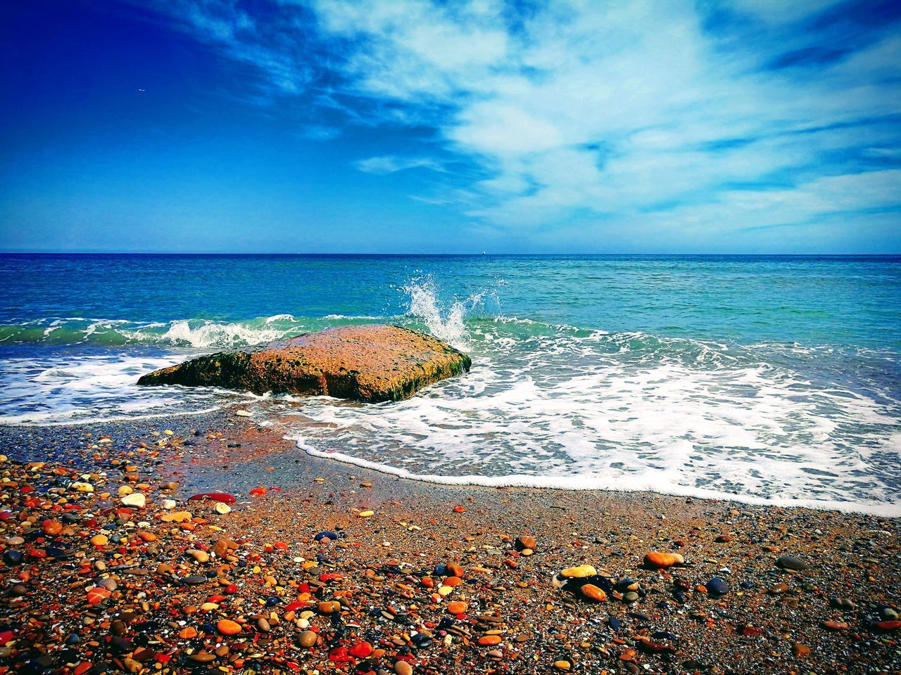 PEBBLES ON BEACH AGAINST BLUE SKY