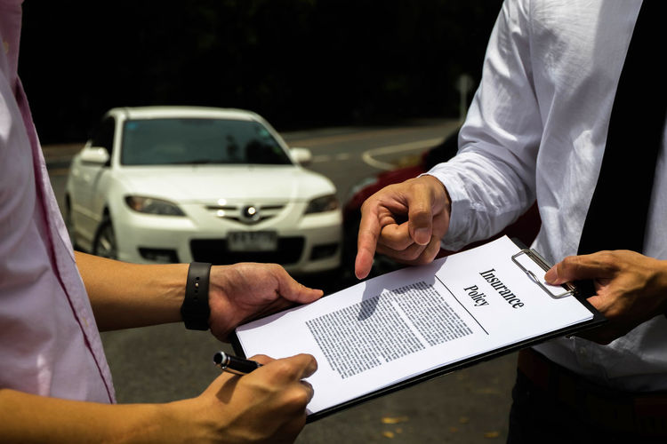 Midsection of man signing insurance document with agent standing on road