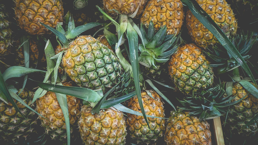 Abundance Close-up Day Food Food And Drink For Sale Freshness Fruit Green Color Healthy Eating Large Group Of Objects Market No People Outdoors Pineapple Retail  Retail Display Ripe Still Life Tropical Fruit Wellbeing