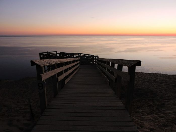 Pier leading towards sea against sky during sunset