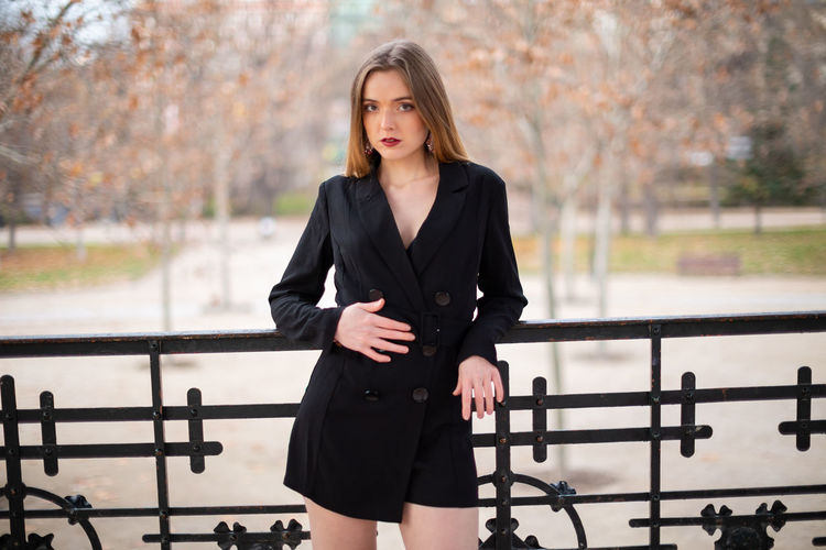 Pretty model woman posing in a park resting on a fence Woman Fence Park Leaning Businesswoman Employee Looking At Camera Young Adult Lifestyle Leisure Rest Elegant Relax Female Style Trendy Calm Fashion Model Pretty Beautiful Attractive Makeup Lady Portrait