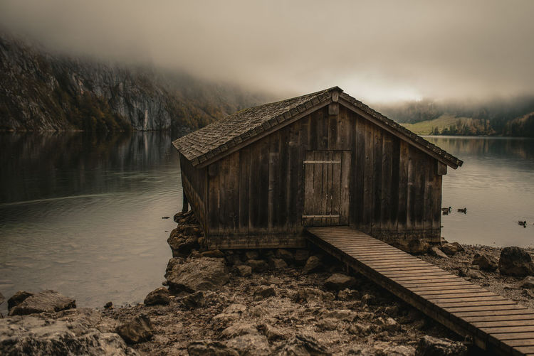 Log cabin by lake during foggy weather