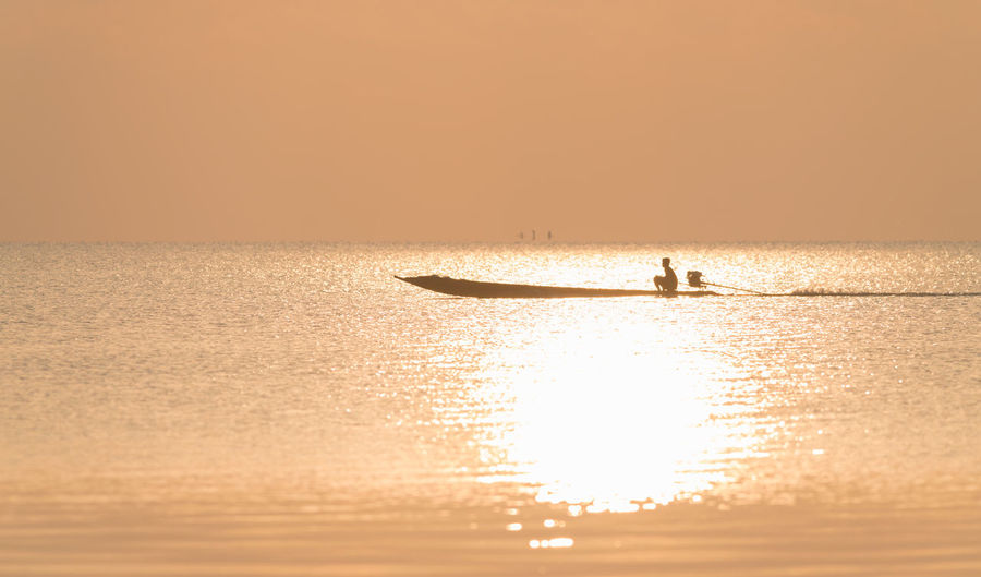 Silhouette man on boat in sea against clear sky during sunset