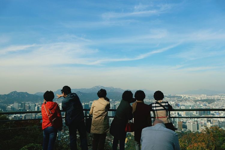 Rear view of people looking at cityscape against sky
