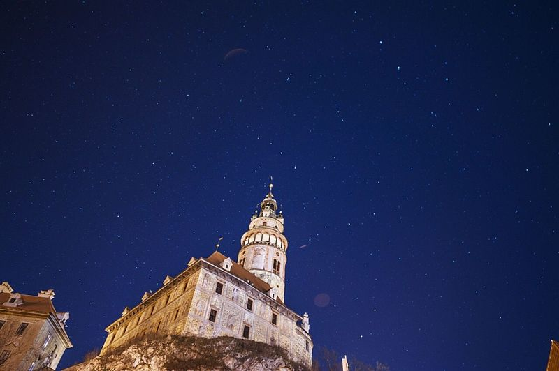 Low angle view of castle against star field in blue sky at night