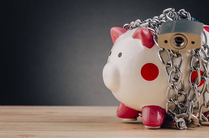 piggy bank surrounded by chains and padlock on wooden desk Indoors  No People Close-up Still Life Table Red Animal Representation Piggy Bank Art And Craft Representation Wood - Material Savings Creativity Focus On Foreground Wall - Building Feature Investment Single Object Animal Craft Copy Space Personal Accessory Care