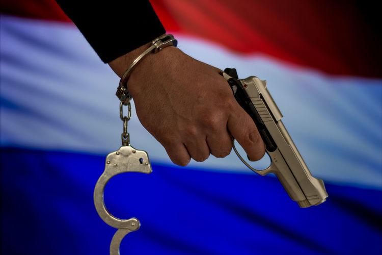 Cropped hand with handcuffs holding gun against dutch flag
