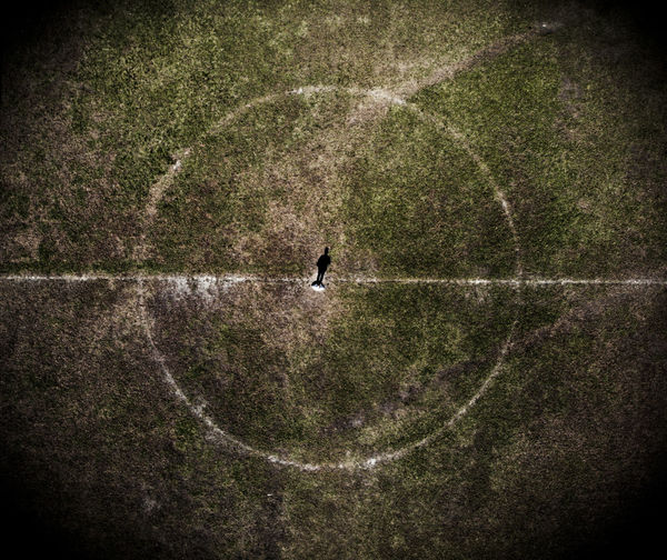 High angle view of silhouette person standing on soccer field