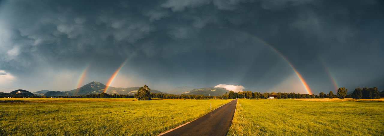 Panoramic image of glowing double rainbow above fields and road in salzburg, austria