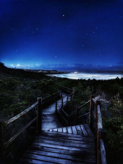Footbridge amidst trees against sky at night