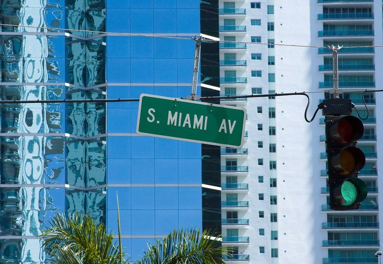 Close-Up Of Road Sign Against Buildings