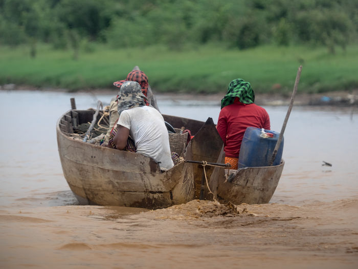 Rear view of men sitting in boat on shore