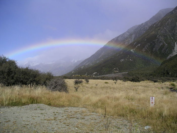 Scenic view of rainbow over grassy field
