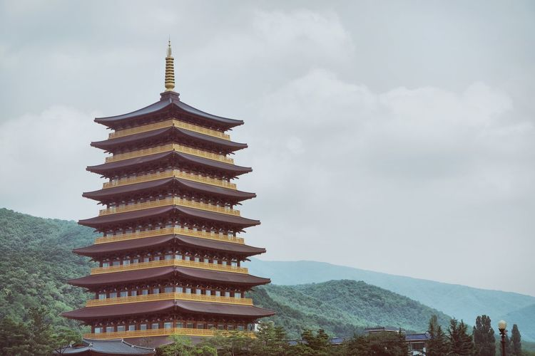Temple by mountain with sky in background