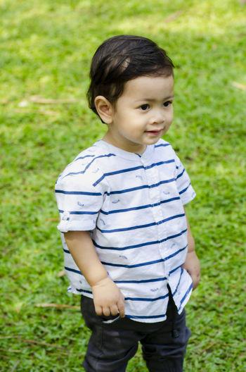 Cute boy standing on field