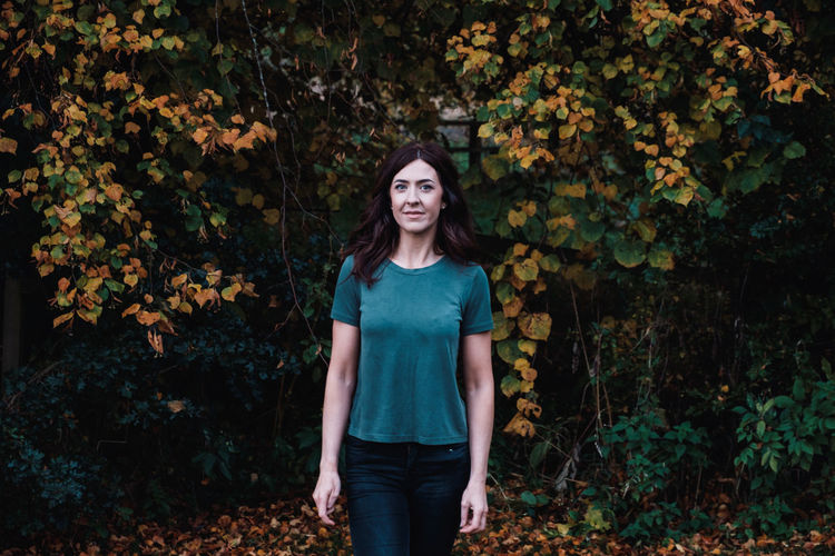Portrait of a beautiful young woman standing in autumn