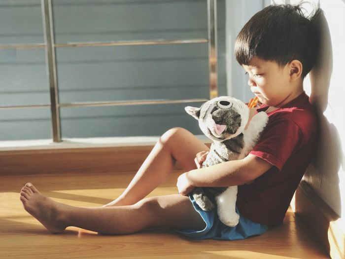 Cute Boy Sitting With Stuffed Toy Cat At Home