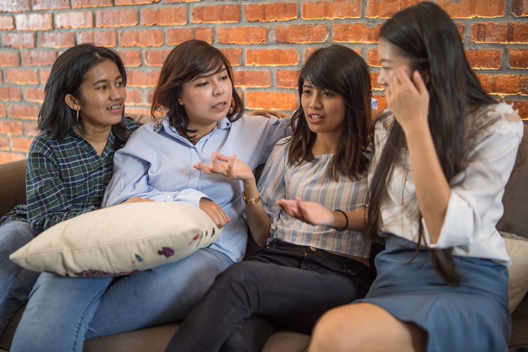 Female friends discussing while sitting on sofa at home