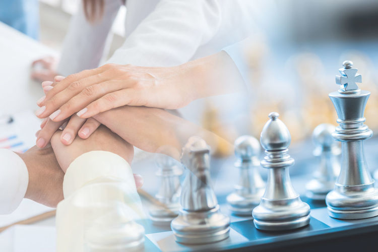 Double exposure of business people stacking hands and chess pieces