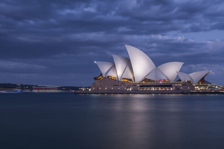 Illuminated Sydney Opera House By Harbor Against Cloudy Sky At Night