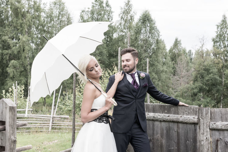 Bride With Groom Holding Umbrella Against Trees