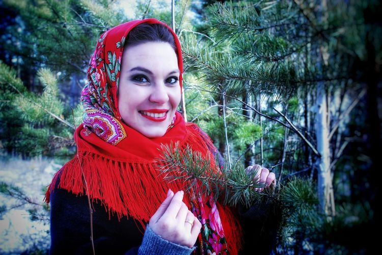 Portrait of beautiful young woman standing against red trees