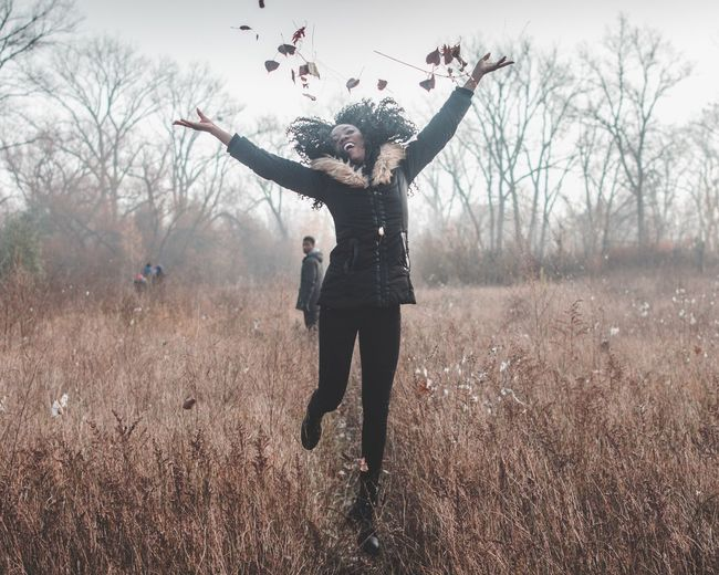 Full Length Of Woman Jumping While Throwing Dry Leaves On Field