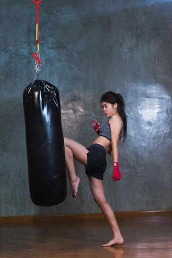 Full length of female boxer kicking punching bag