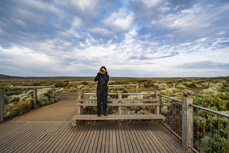 Man standing on railing against sky