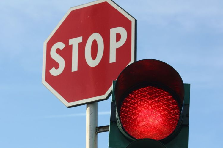 Low angle view of stop sign by illuminated red light against sky