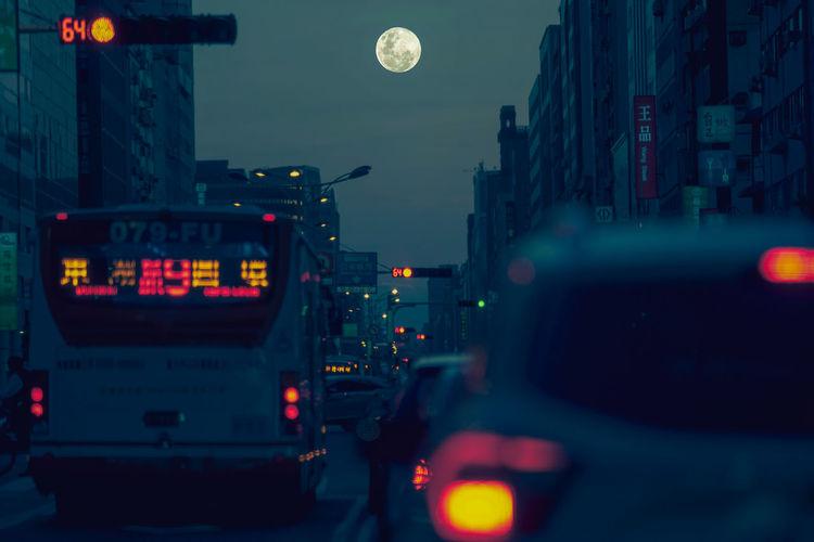 Illuminated city street against sky at dusk