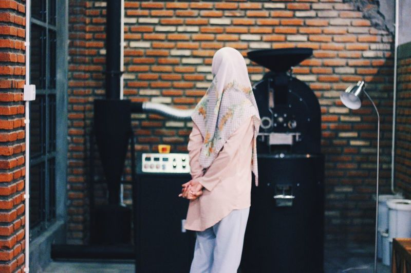 Rear view of woman walking against brick wall