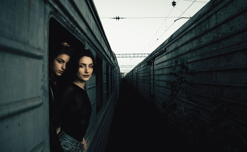 Portrait of young women peeking out from train window