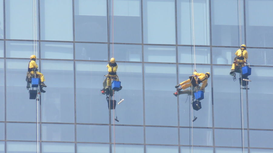 Low angle view of window washers cleaning office building