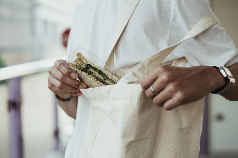 Midsection of person putting sandwich in bag