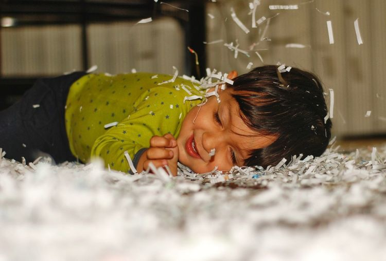 Side View Of Child Lying Down On Papers
