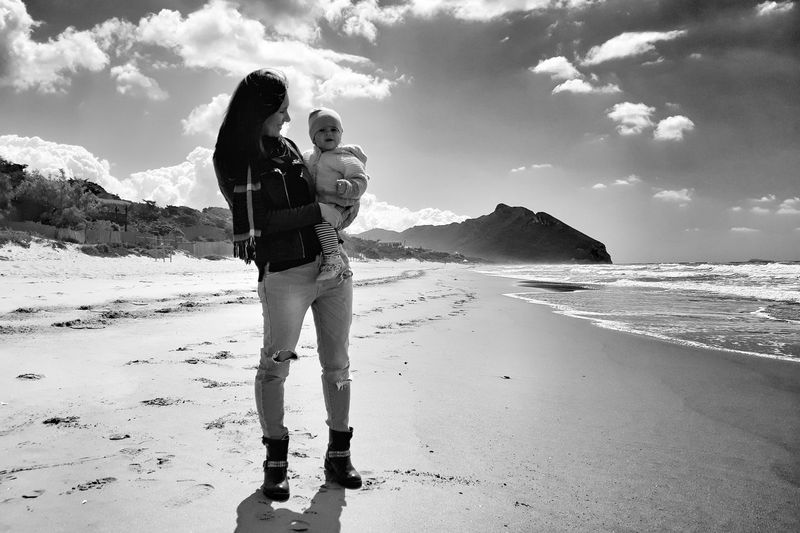 Mother carrying daughter at beach against sky
