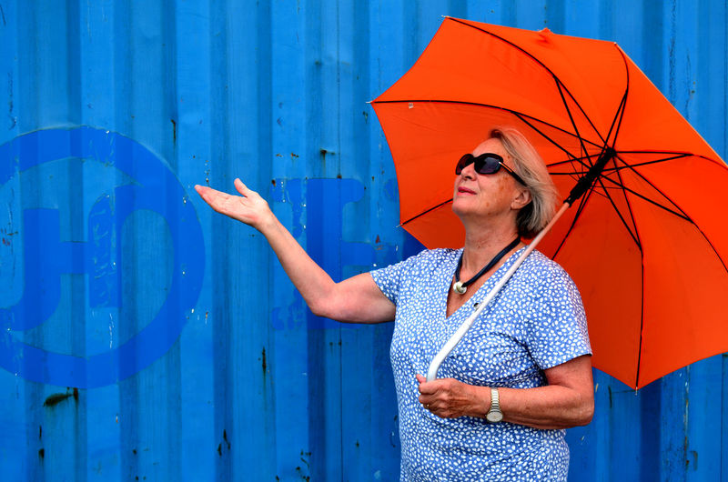 Close-up Blue Orange Color Umbrella Women One Person Standing Protection Security Holding Lifestyles Real People Adult Leisure Activity Waist Up Day Casual Clothing Front View Outdoors Human Arm Rain Arms Raised Elderly Woman Sunglasses