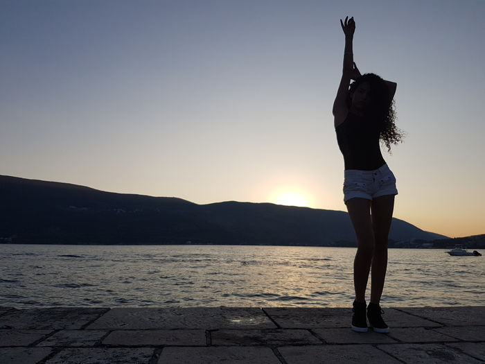 Full Length Of Woman Standing On Harbor Against Clear Sky During Sunset