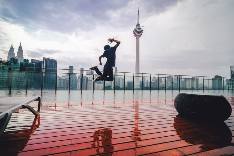 Man in mid-air at balcony against city