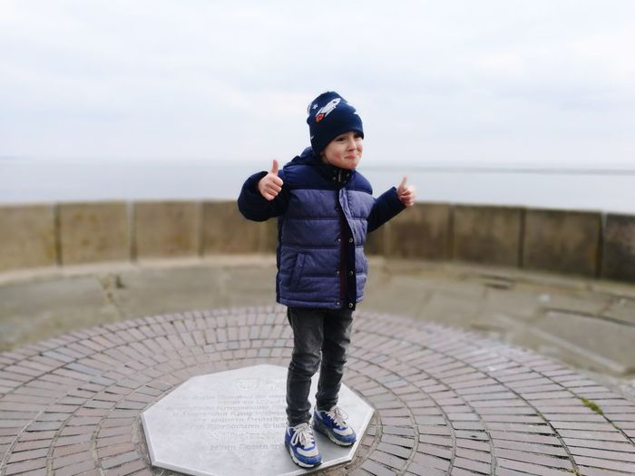 Full length of boy standing at observation point against sky