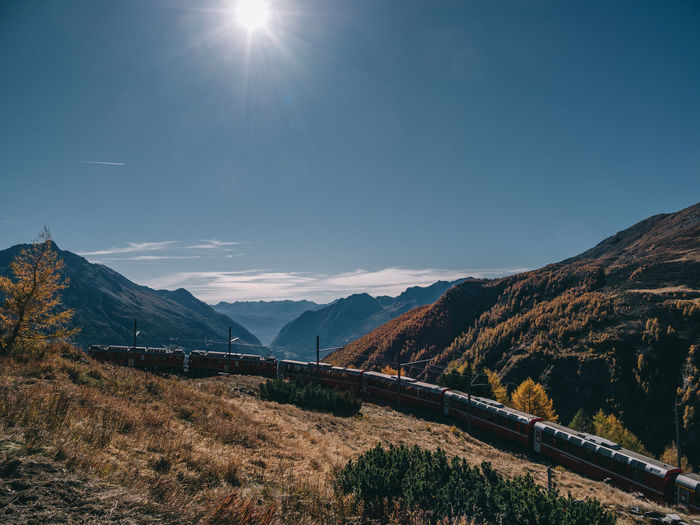 Train passing by mountains on sunny day