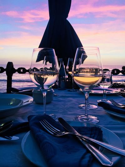 Close-up of wineglasses on restaurant table at beach against sky during sunset