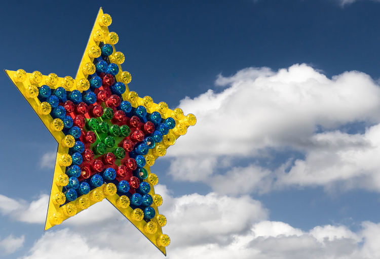 Low angle view of colorful star shape lighting equipment against sky
