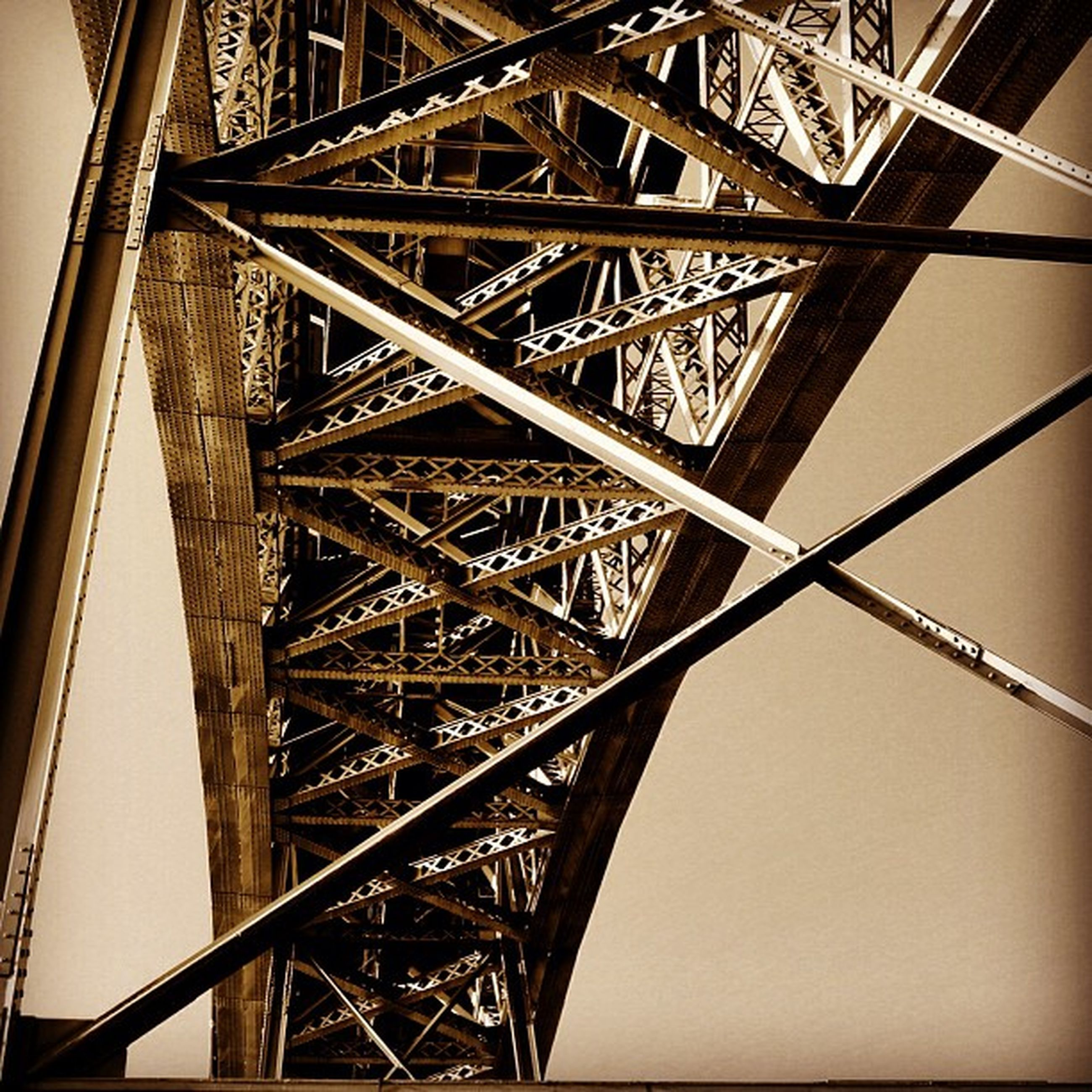 built structure, architecture, metal, low angle view, engineering, connection, metallic, eiffel tower, international landmark, bridge - man made structure, tower, famous place, clear sky, travel destinations, grid, tall - high, sky, no people, capital cities, outdoors